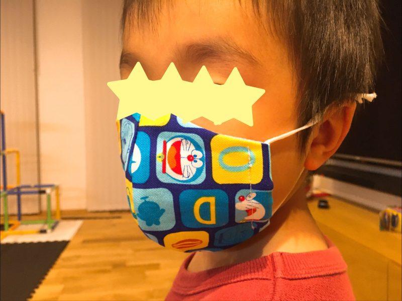 ドラえもんの生地をつかったマスクを装着した子供